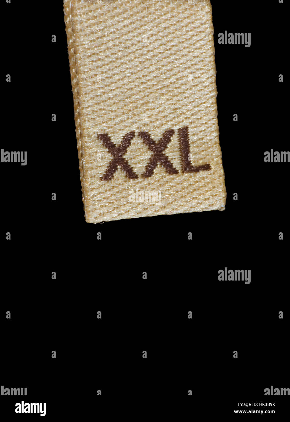 Macro XXL size clothing label, beige, brown, isolated vertical closeup Stock Photo