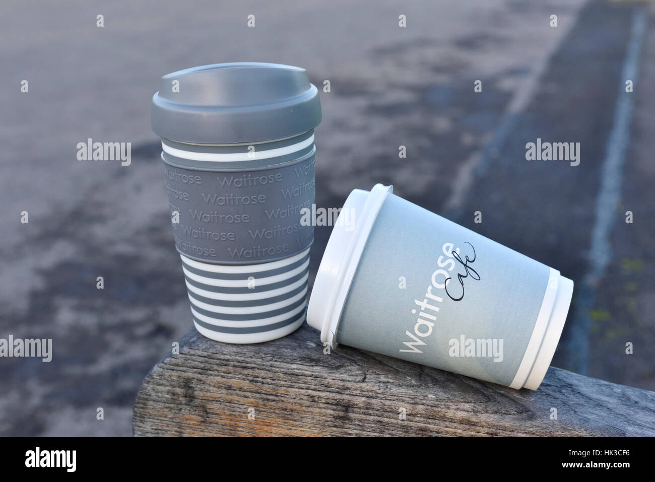 Waitrose disposable and reusable take away coffee cups or travell mug on park bench, Central London, England, UK - Stock Image