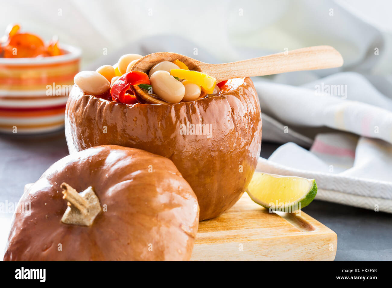 White bean and red pepper vegetables stew in pumpkin bowls served on wooden board - Stock Image
