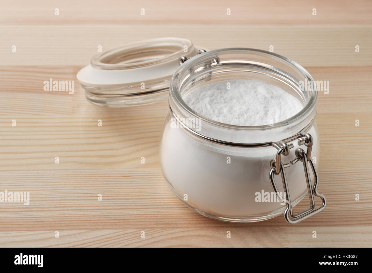 Open glass jar of baking soda on wooden background - Stock Image