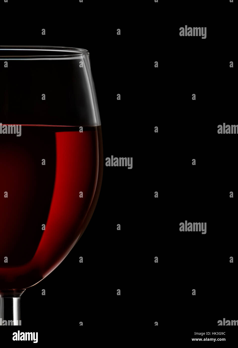 Close up of red wine glass on black background - Stock Image