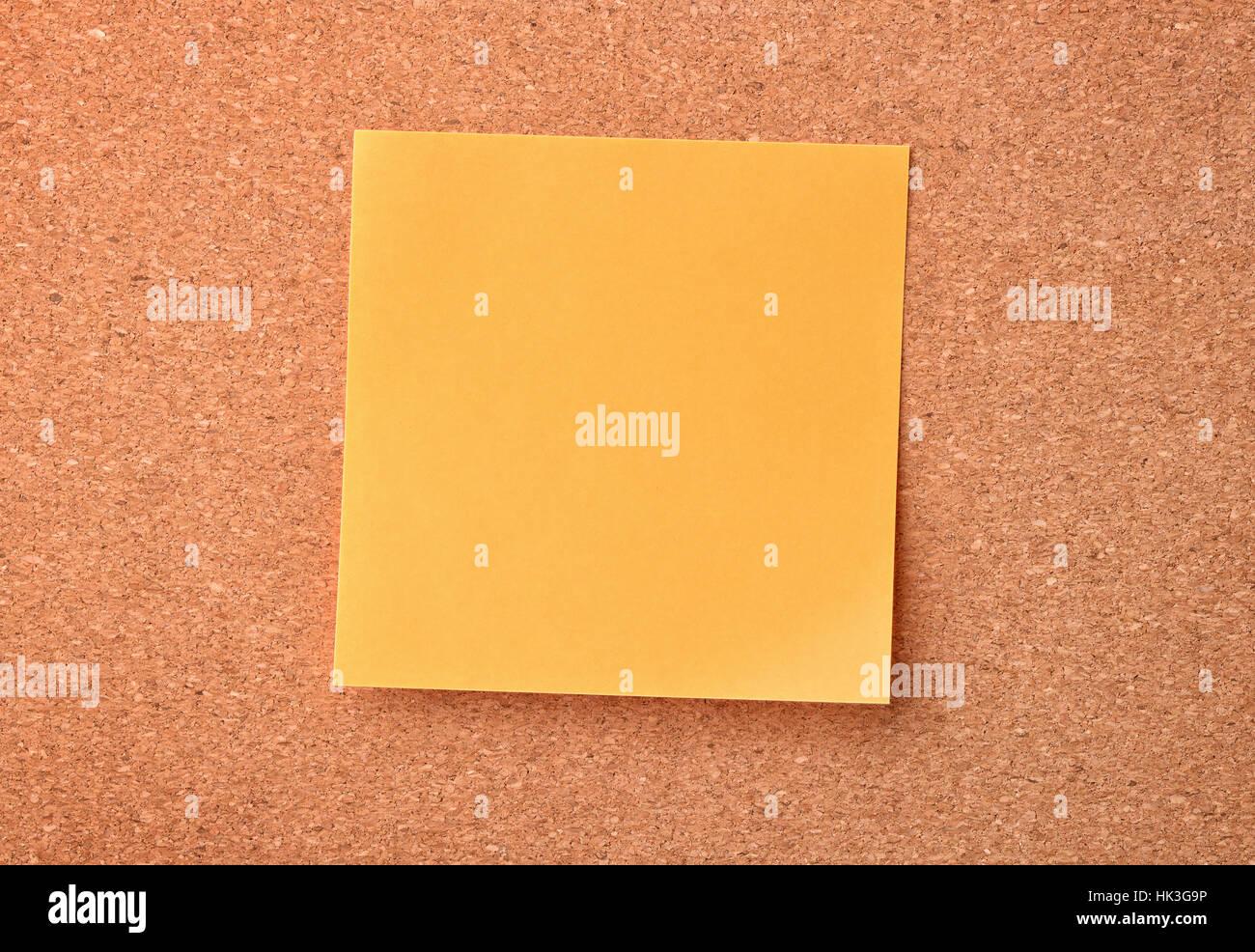 Orange sticky note on cork board - Stock Image