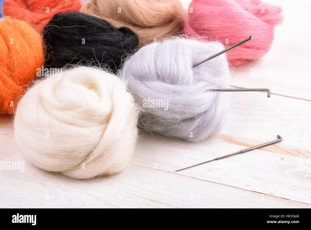 Close up of wool needle felting kit on wooden surface - Stock Image
