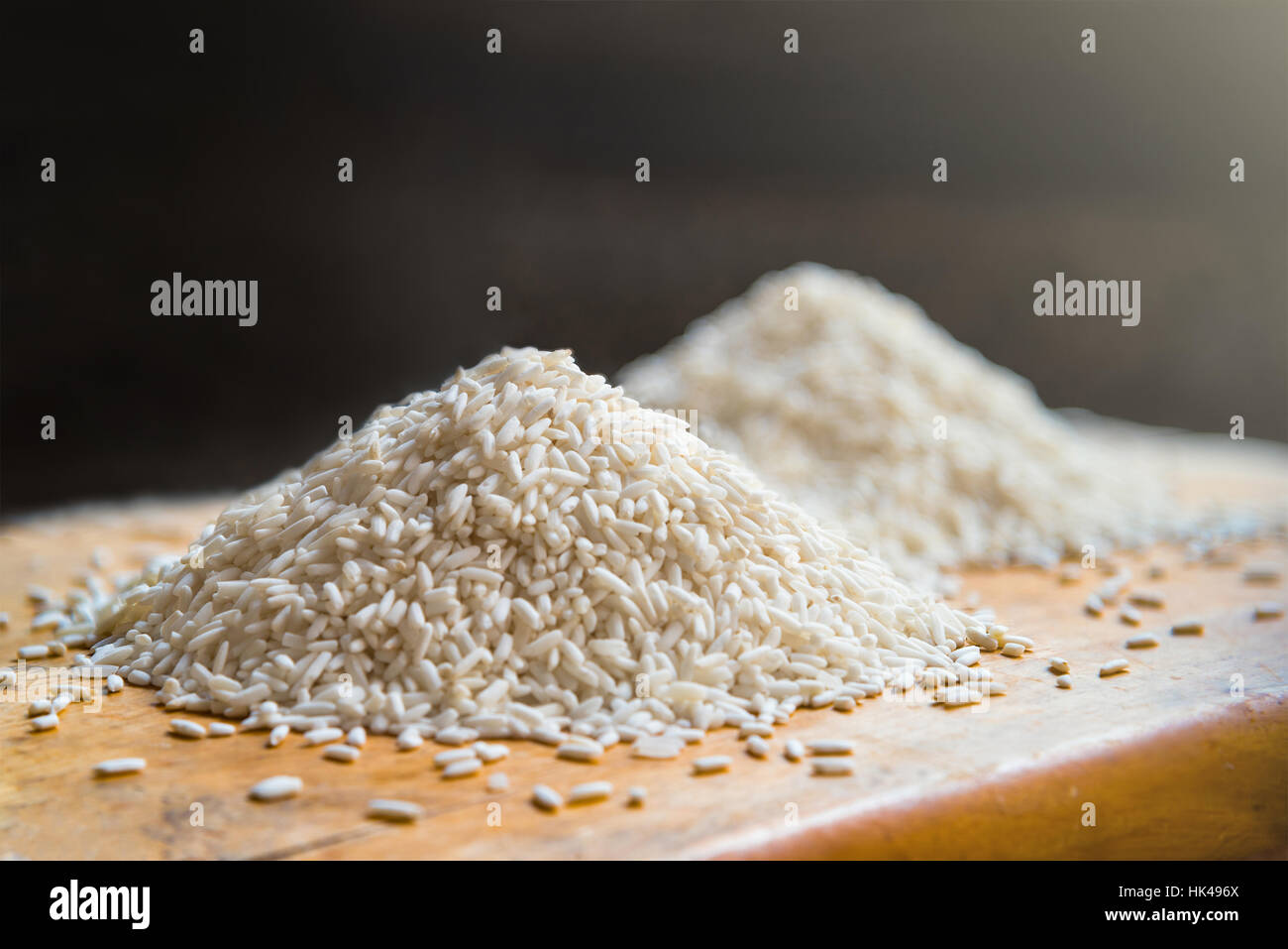 Two piles of white rice on wooden table background, metaphor ingredient, nutrition, carbohydrate food, agriculture - Stock Image