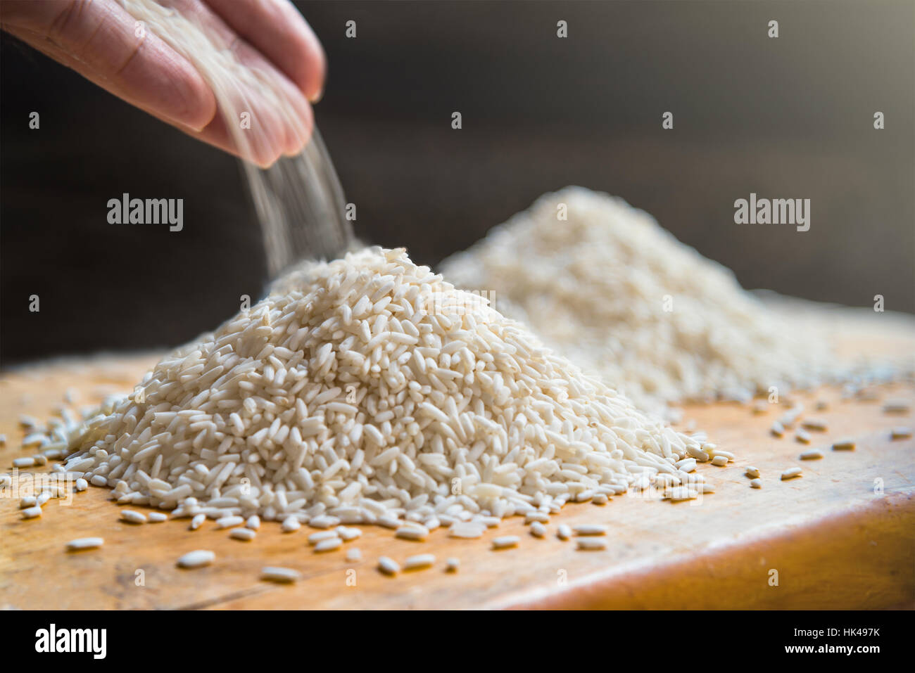 Hand pouring rice on pile of white rice on wooden table background, metaphor ingredient, nutrition, carbohydrate - Stock Image