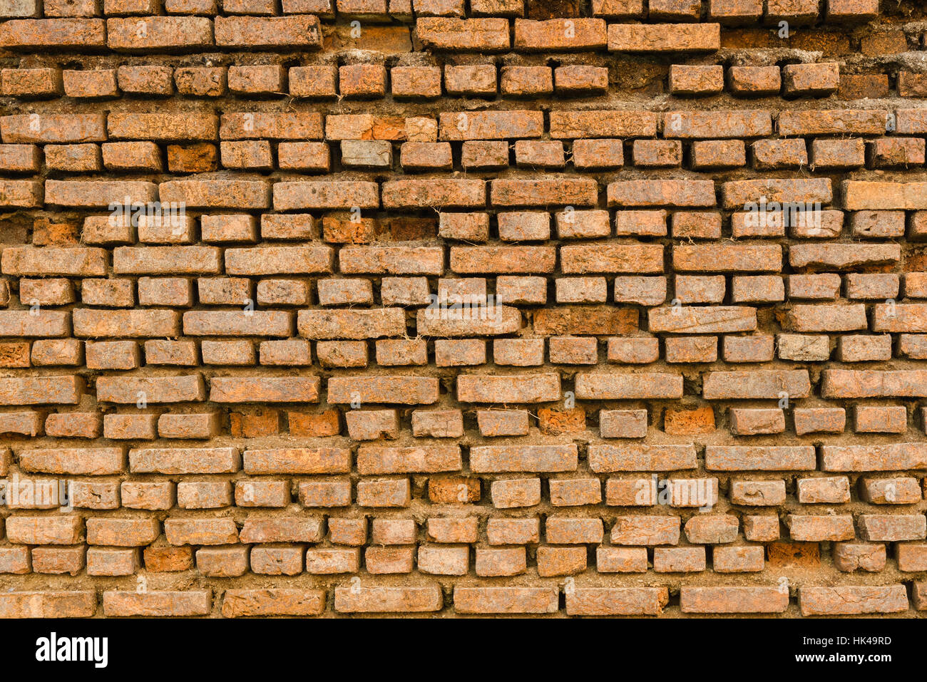 Old Ancient Vintage Grunge Dusty Orange Brick Wall With Some Cracked Bricks Texture Background - Stock Image