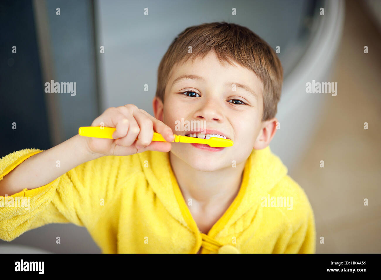 Boy brushing his teeth in bathtub, smiling. healthy lifestyle concept Stock Photo