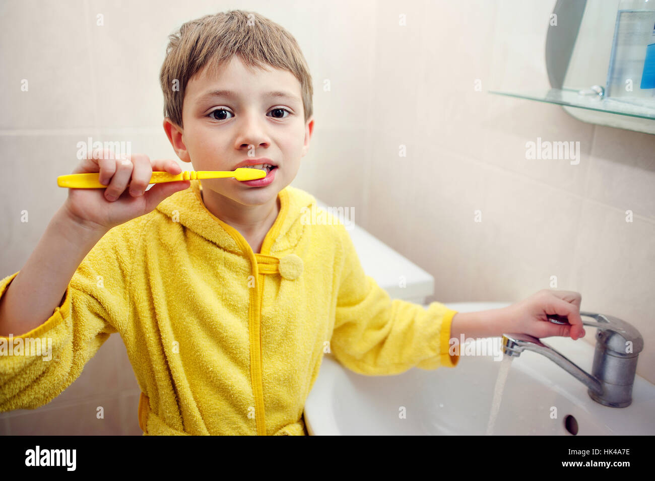 Personal hygiene. Care of an oral cavity. The boy brushes teeth. Stock Photo