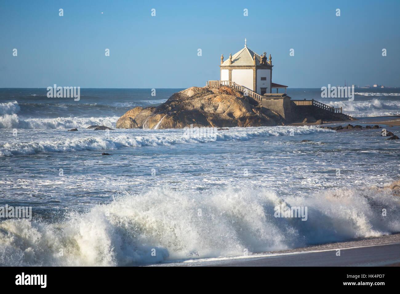 Ocean surf and Chapel Senhor da Pedra at Miramar Beach, near Porto, Portugal. - Stock Image