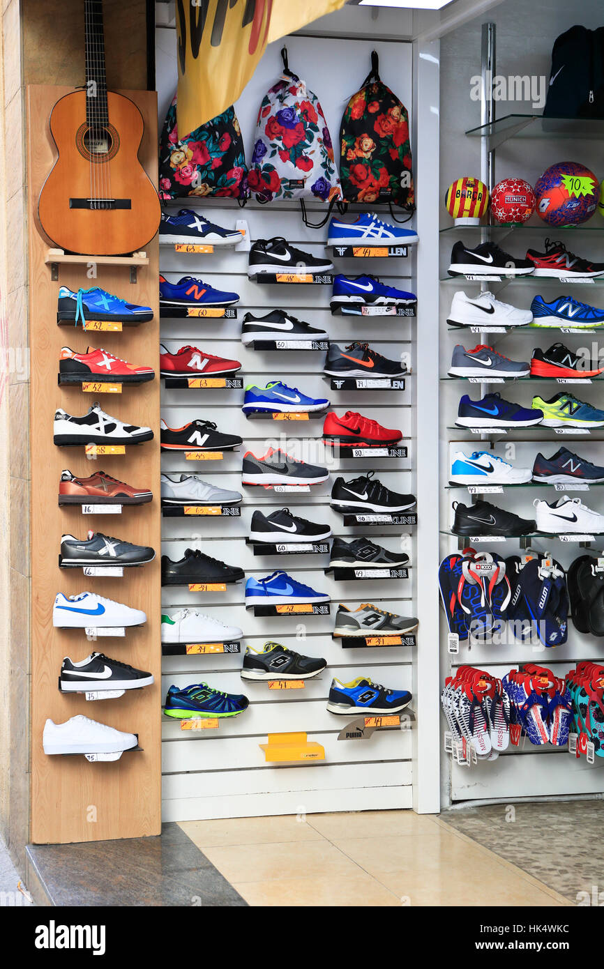 Running shoes on display in a sports apparel store - Stock Image