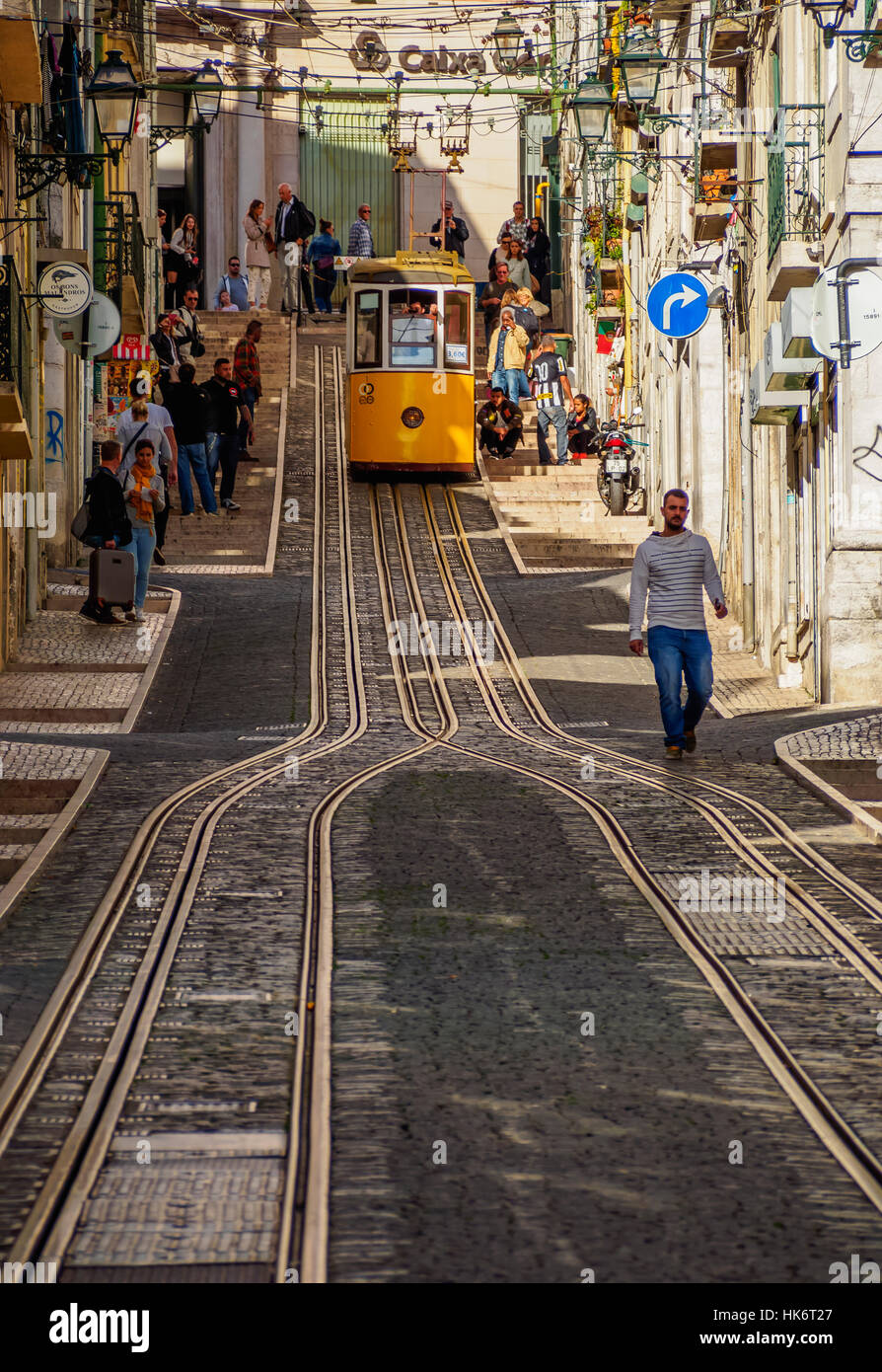 Busy street with yellow funicular railway in city centre, Bica Funicular, Elevador da Bica, Lisbon, Portugal - Stock Image