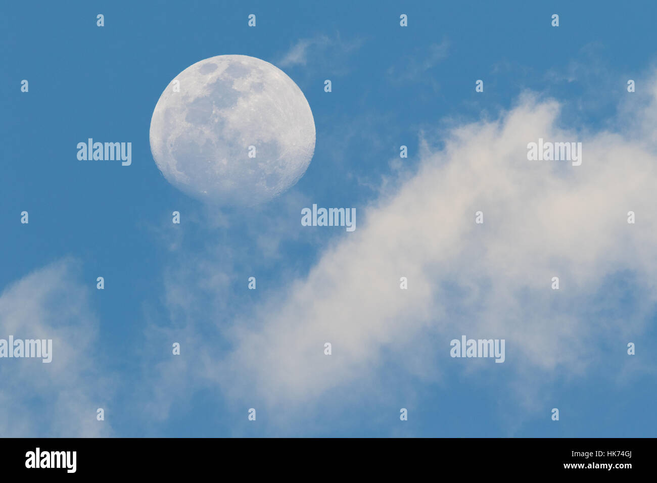 moon and clouds in daylight - Stock Image