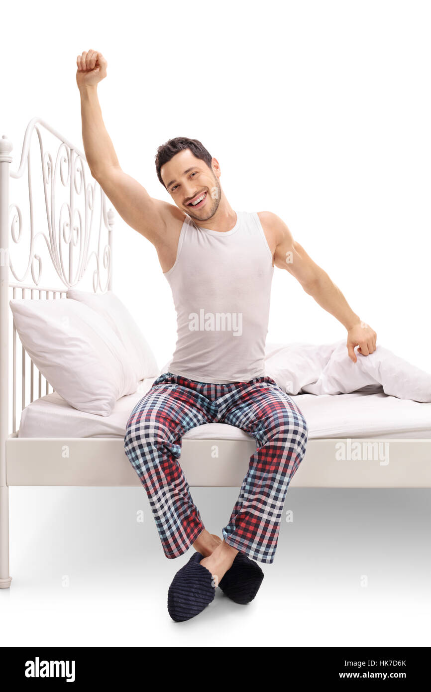 9d8245db6e Man in pajamas sitting on a bed and stretching himself isolated on white  background