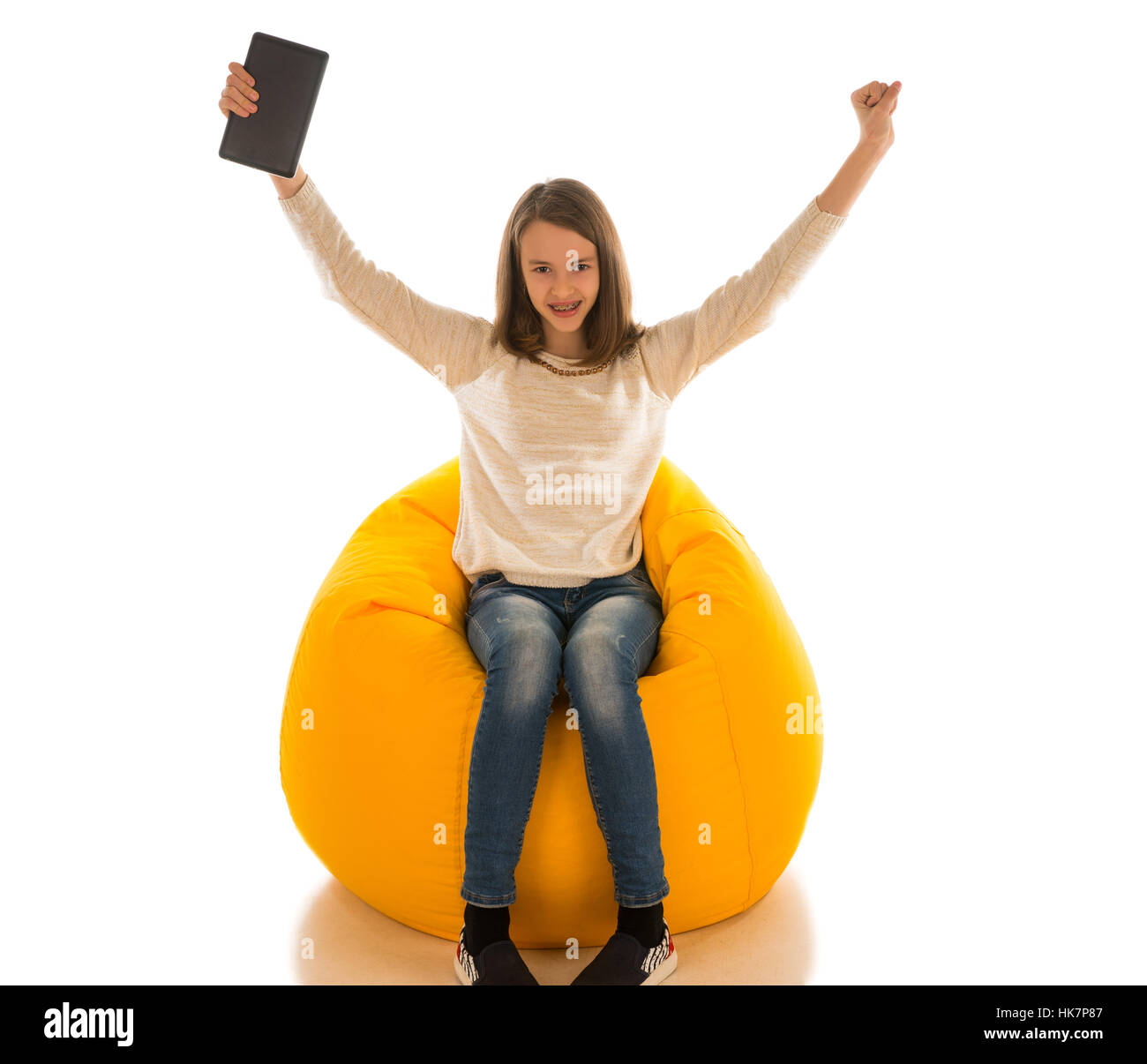 Young cute girl put her hands up and holding the tablet while sitting on yellow beanbag isolated on white background - Stock Image