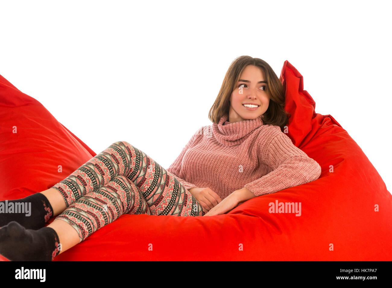 Young woman lying on red square shaped beanbag sofa chair for living room or other room isolated on white background - Stock Image