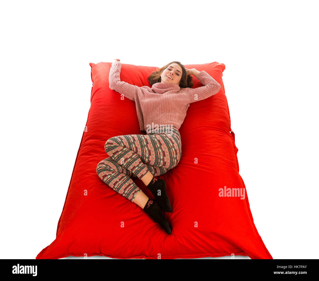 Attractive woman lying on red square shaped beanbag sofa for living room or other room isolated on white background - Stock Image