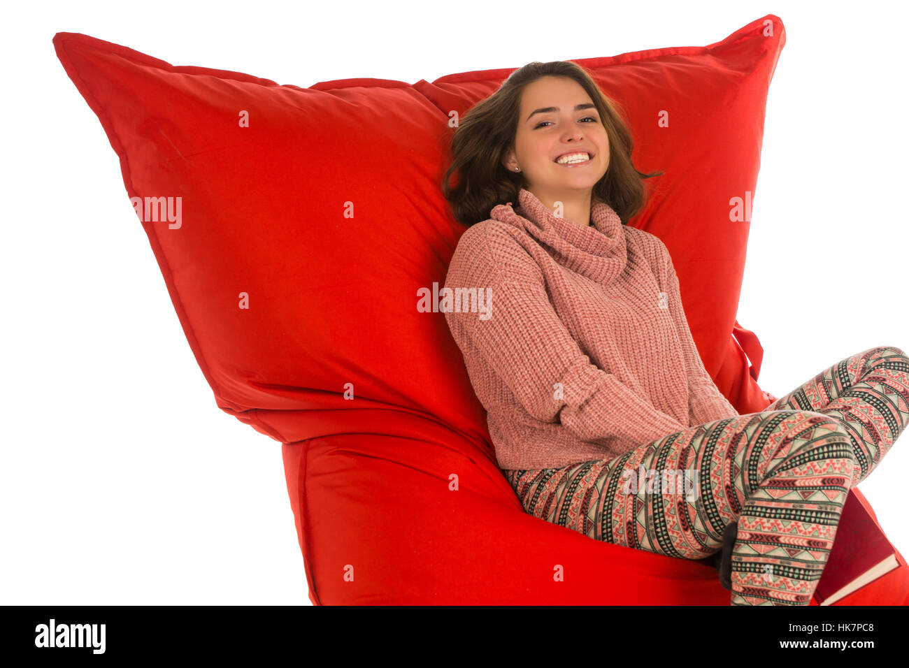 Smiling young woman sitting on red beanbag sofa chair for living room or other room and holding a book isolated - Stock Image