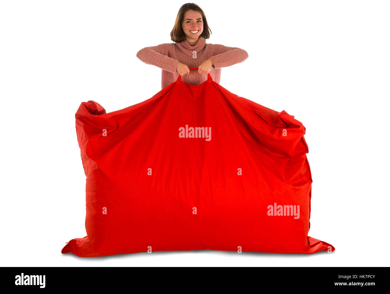 Young smiling woman standing and holding red rectangular shaped beanbag sofa chair for living room or other room - Stock Image