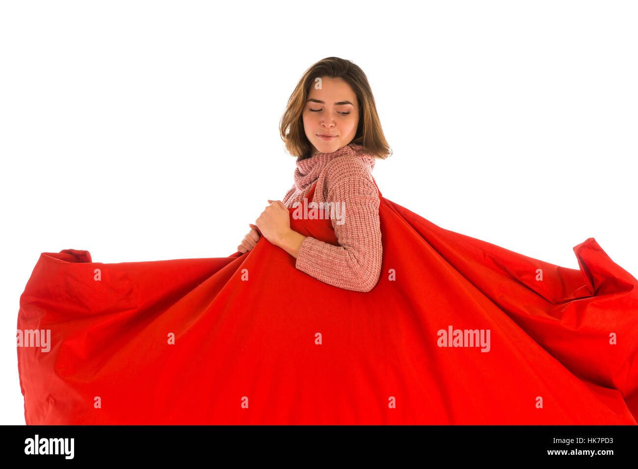 Young woman holding on her shoulder red rectangular shaped beanbag sofa chair for living room or other room isolated - Stock Image