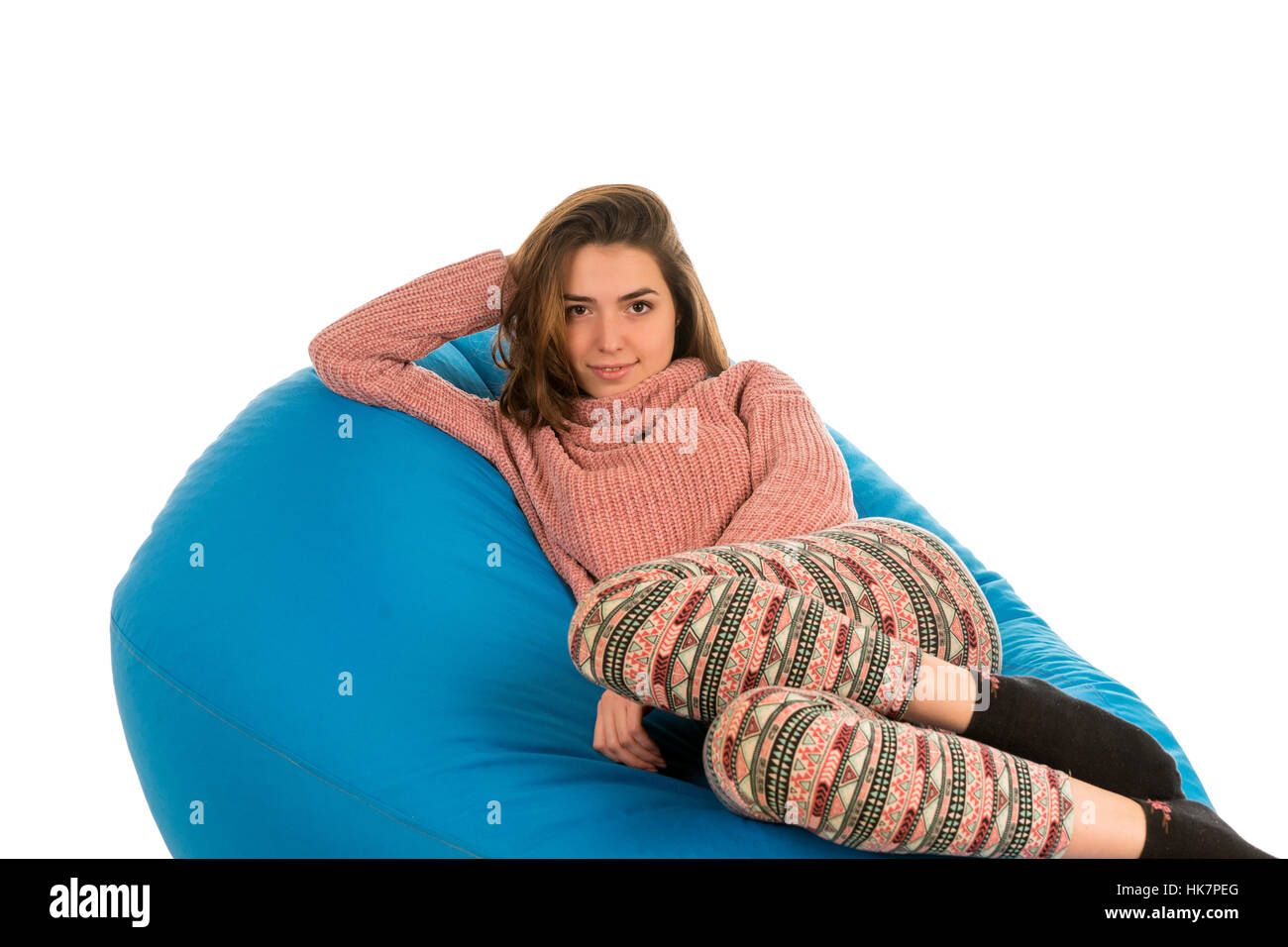 Beautiful woman lying on blue beanbag sofa for living room or other room isolated on white background - Stock Image