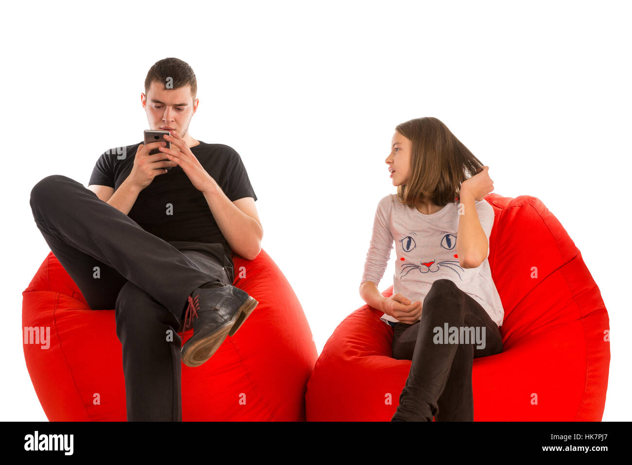Young man and girl sitting on red beanbag chairs isolated on white background - Stock Image