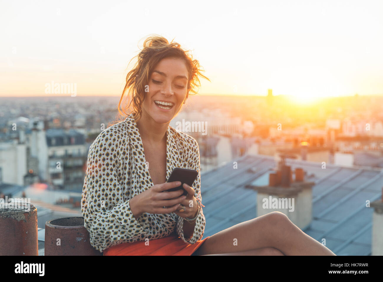 Woman using a smart phone on the roofs of Paris - Stock Image