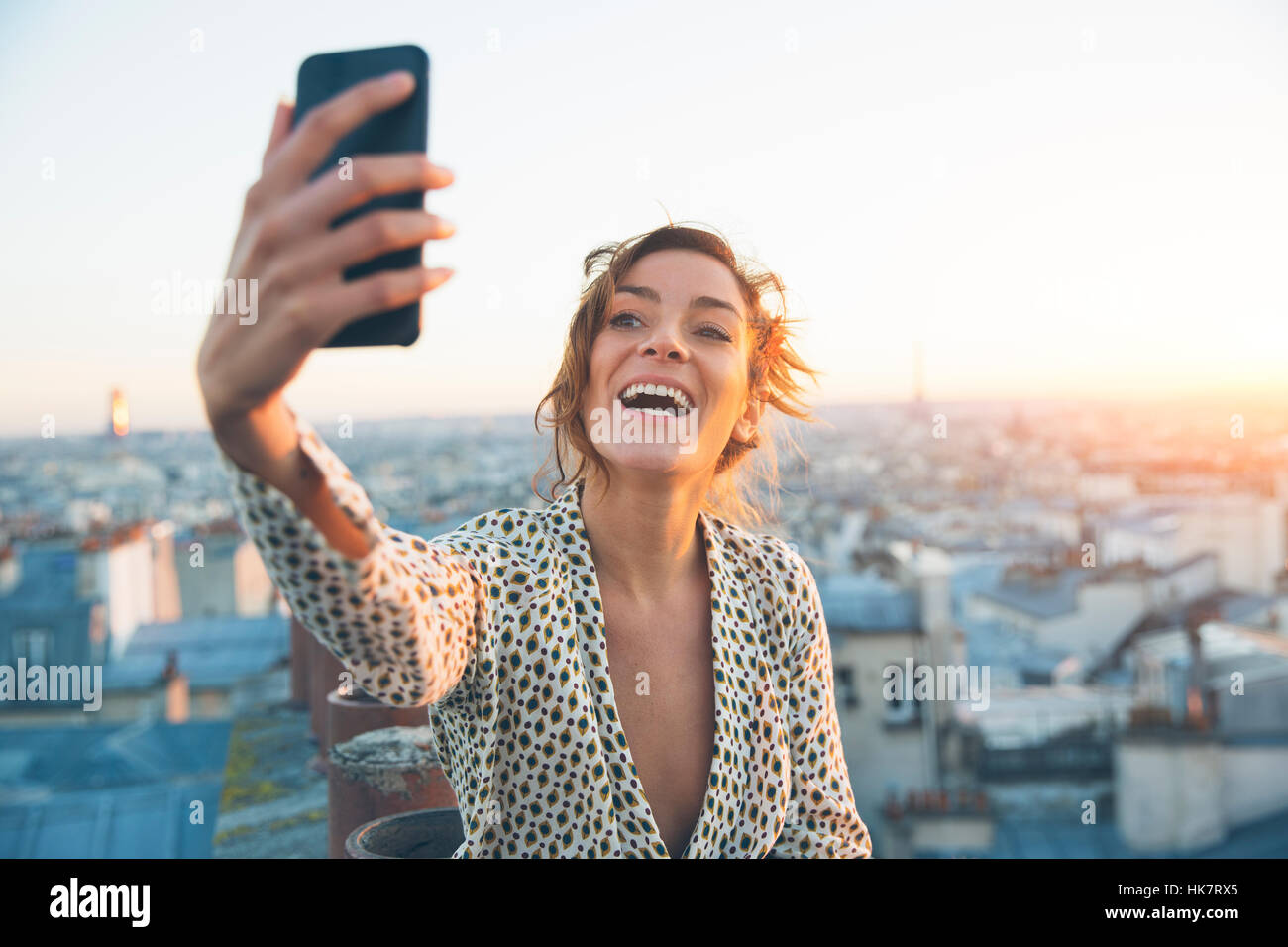 Woman doing a selfie on the roofs of Paris - Stock Image
