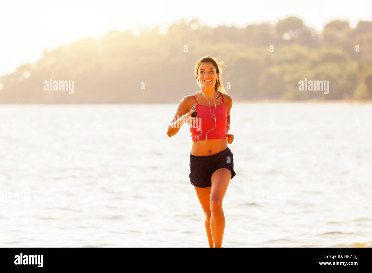 young healthy lifestyle woman running on beach - Stock Image