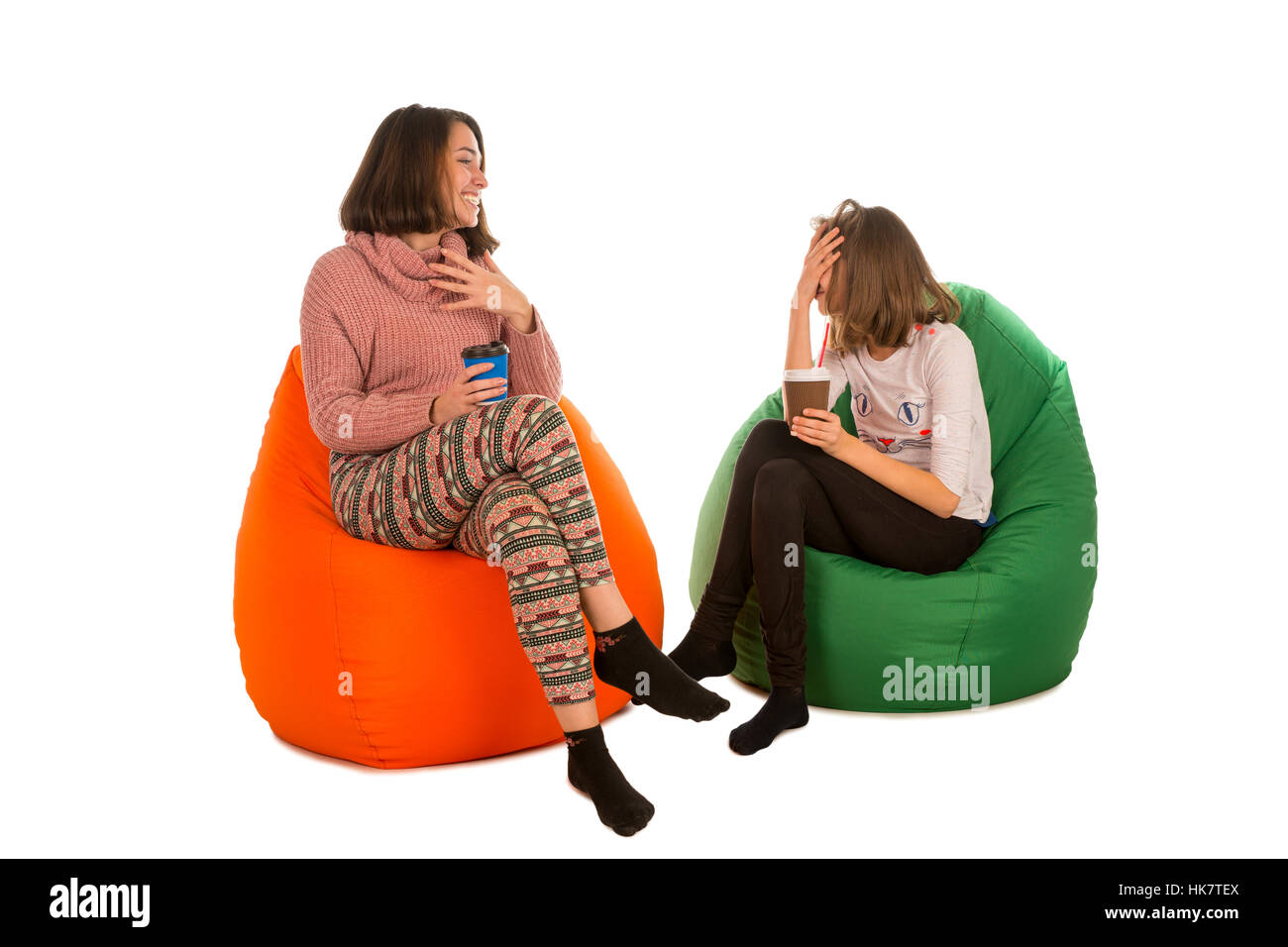 Young Cute Woman And Laughing Girl Sitting On Beanbag Chairs And Drinking  Coffee Isolated On White