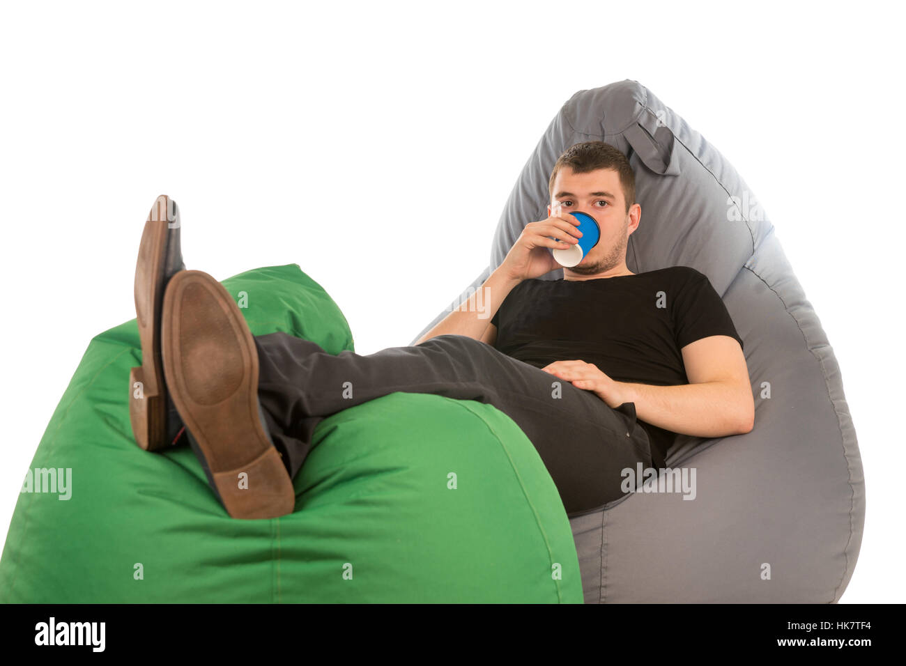 Young man lying on beanbag chairs and drinking coffee isolated on white background - Stock Image