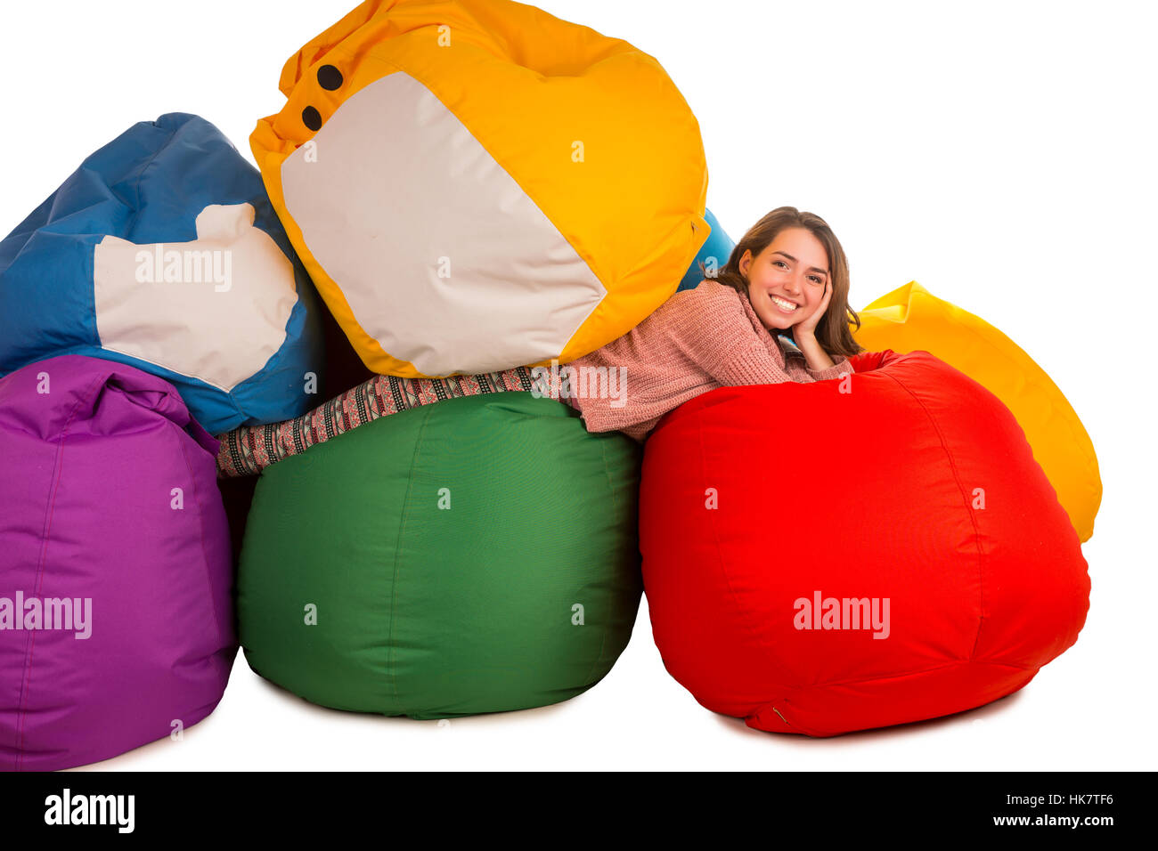 Young smiling woman lying between beanbag chairs isolated on white background - Stock Image