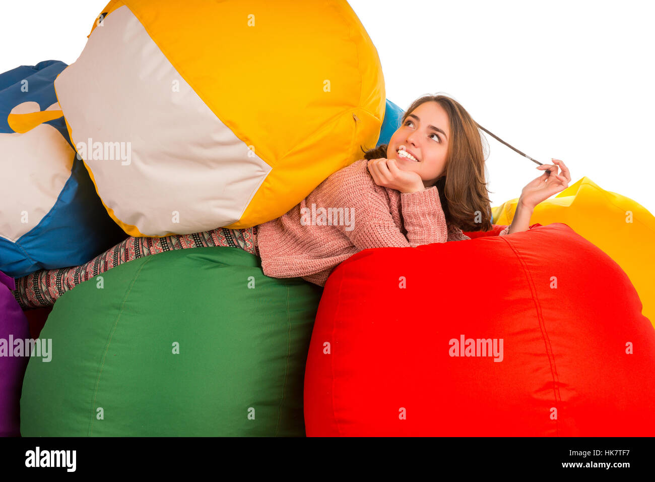 Young dreaming woman lying between beanbag chairs isolated on white background - Stock Image