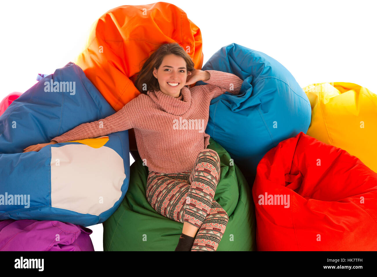 Young cute woman sitting between beanbag chairs isolated on white background - Stock Image