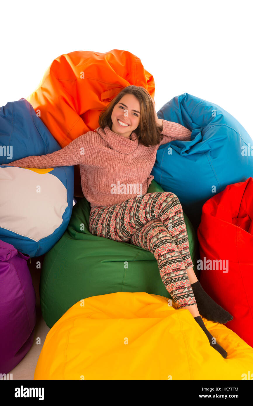 Young cute smiling woman sitting between beanbag chairs isolated on white background - Stock Image