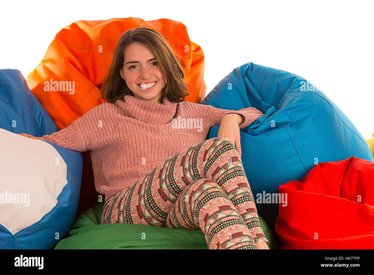 Young happy woman sitting between beanbag chairs isolated on white background - Stock Image
