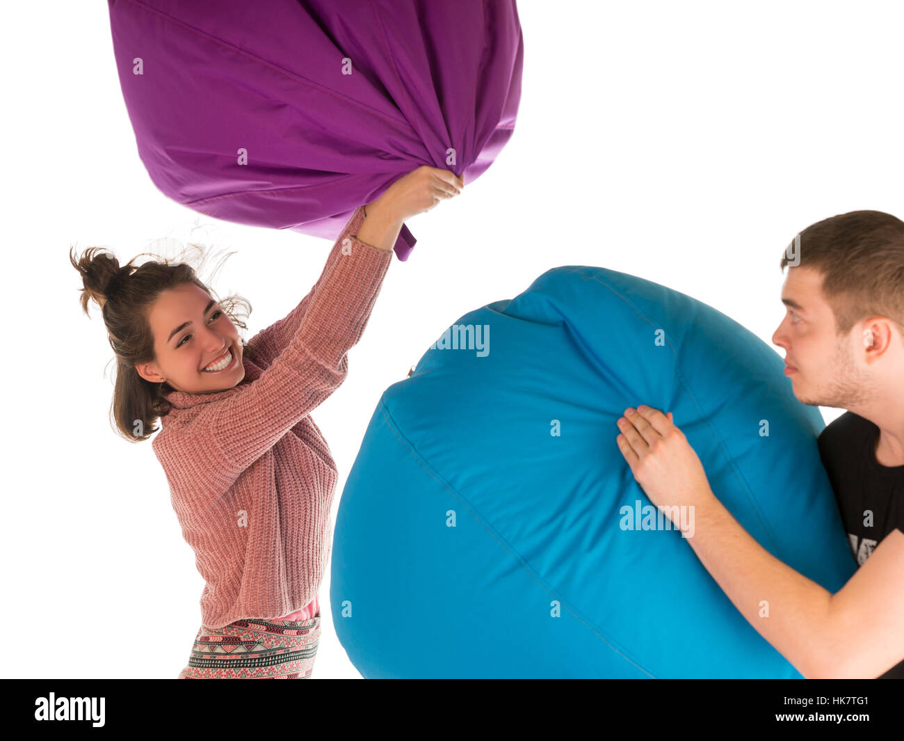 Young funny couple fighting with beanbag chairs isolated on white background - Stock Image