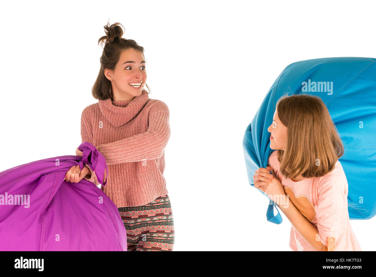 Young funny girls fighting with beanbag chairs isolated on white background - Stock Image