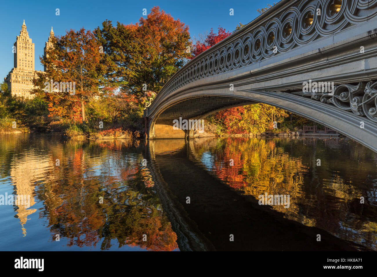 Fall in Central Park at The Lake with the Bow Bridge. Morning view with colorful Autumn foliage on the Upper West - Stock Image