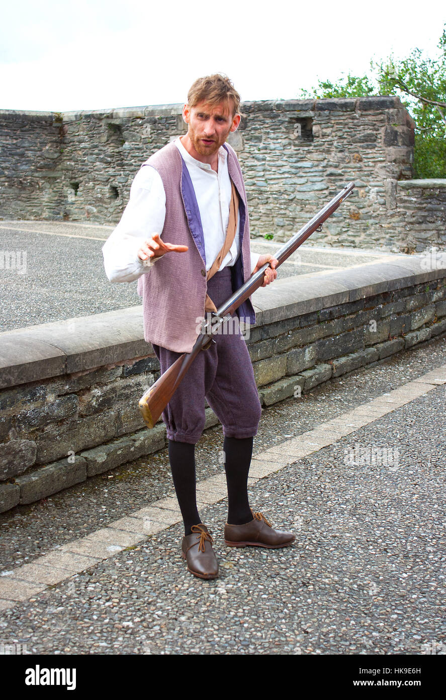 Re-enactment of the historic Siege of Derry in 1688 and this Apprentice Boy with a musket calls for support on the - Stock Image