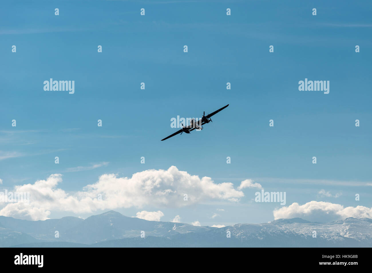 An airoplane B-25 Mitchell is flying in the air, mountains and clouds in the distance - Stock Image