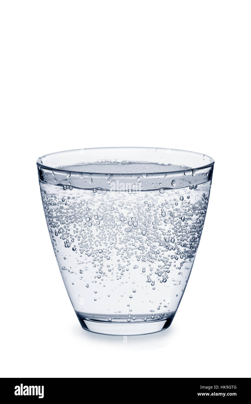 Glass of carbonated water with bubbles on white - Stock Image