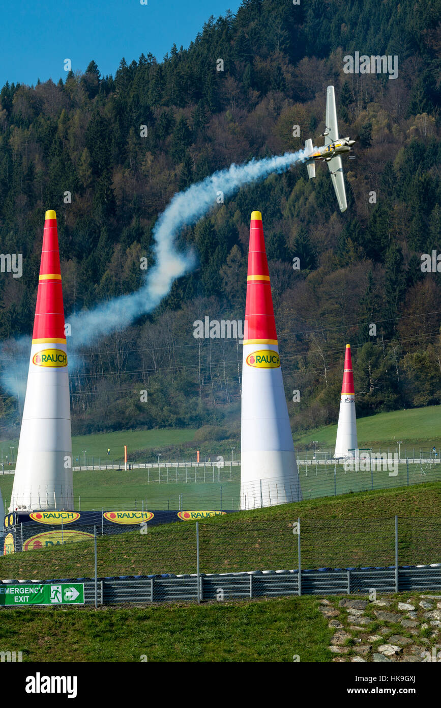 A stunt flying aeroplane, releasing smoke, is flying vertically