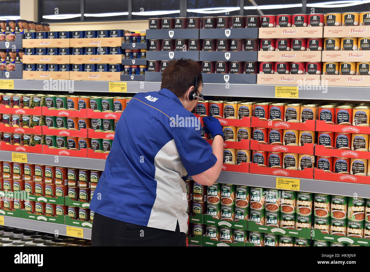 Supermarket shelf stacking tins of soup and stew at Aldi supermarket. - Stock Image