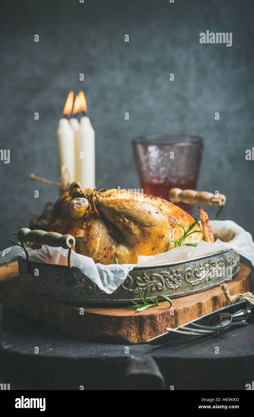 Christmas table set with roasted whole chicken with oranges, bulgur and rosemary, decorative candles, glass of rose - Stock Image
