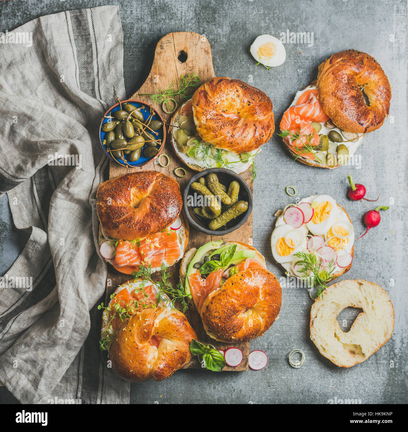 Variety of bagels with smoked salmon, eggs, radish, avocado, cucumber, greens and cream cheese for breakfast, healthy - Stock Image