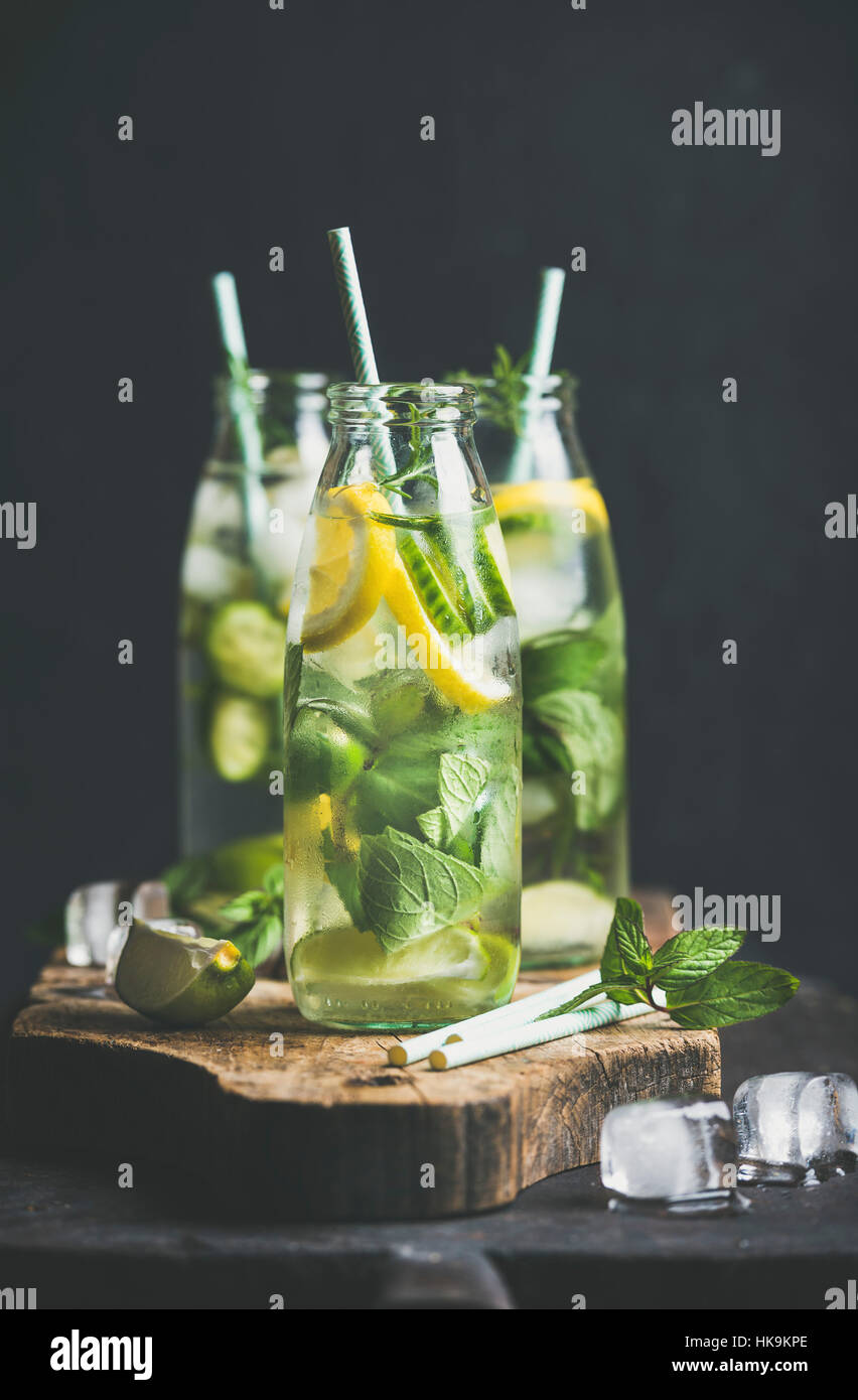 Citrus fruit and herbs infused sassi water for detox, healthy eating or dieting in glass bottles with straws, dark - Stock Image
