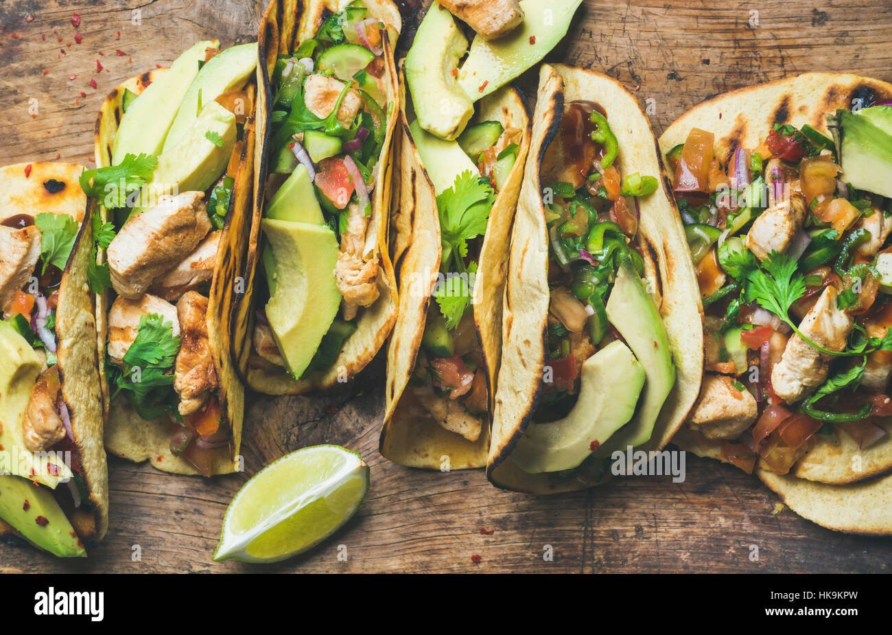 Tacos with grilled chicken, avocado, fresh salsa sauce and limes over rustic wooden background, top view. Healthy - Stock Image