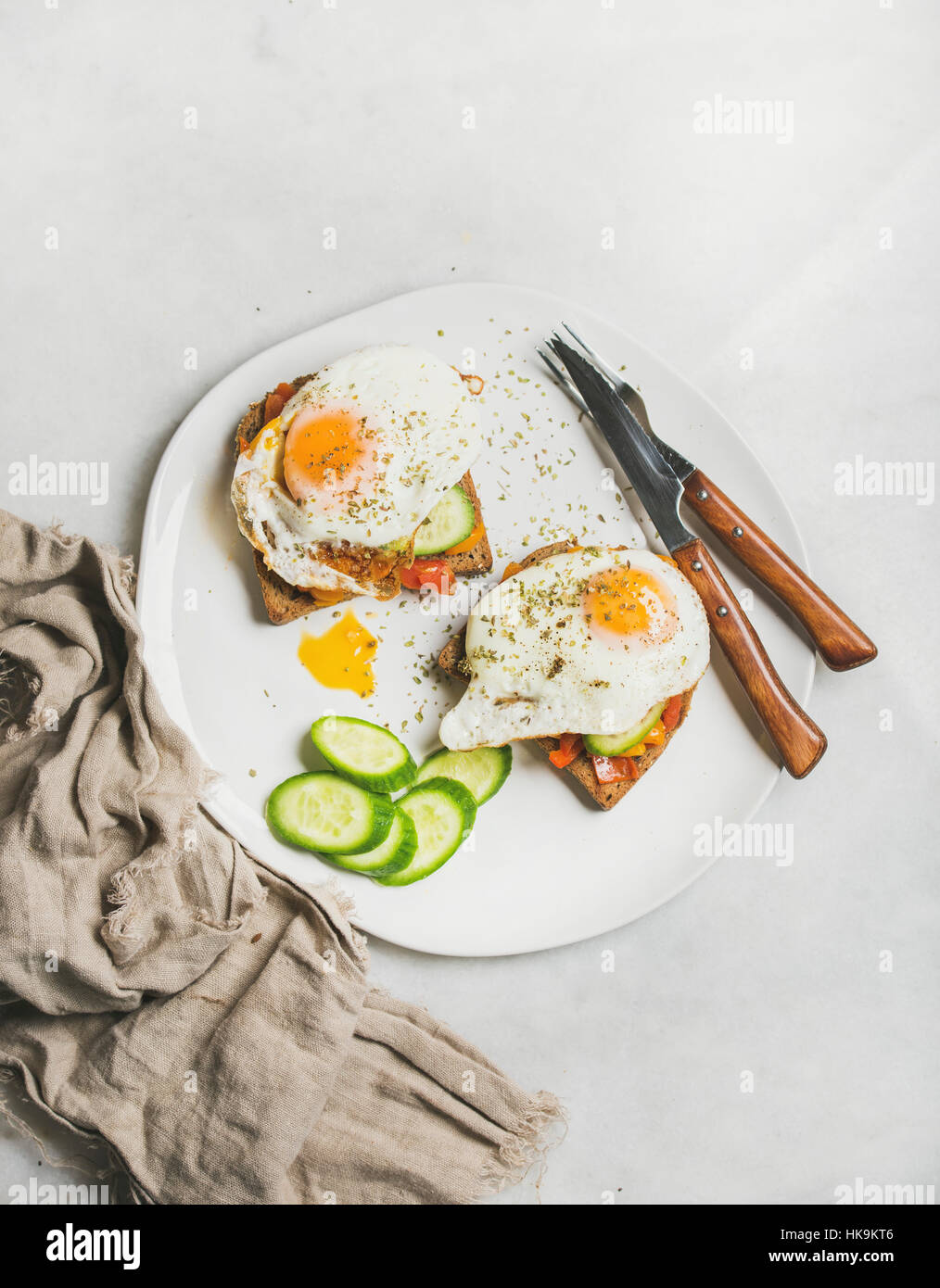 Breakfast toast with fried eggs with vegetables on white plate over grey marble background, top view. Healthy, clean - Stock Image