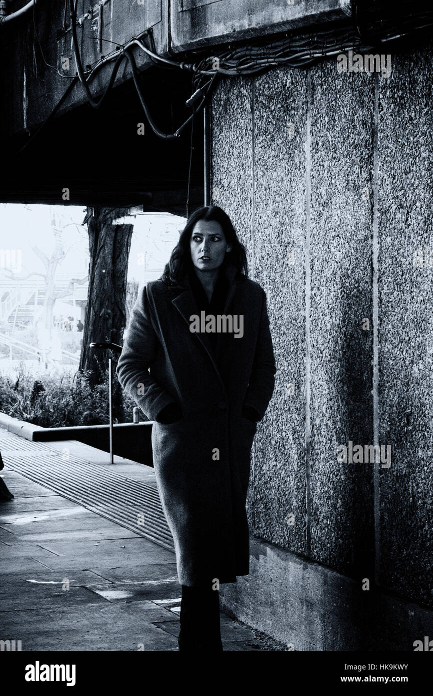 Film Noir style image of vulnerable looking woman walking through an underpass - Stock Image