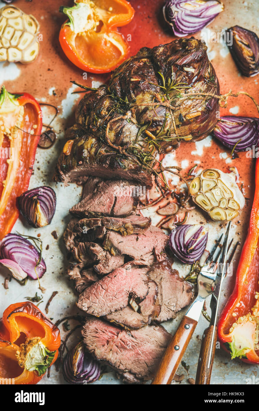 Cooked Roast beef meat with roasted vegetables and herbs in metal baking tray, top view, vertical composition. Slow - Stock Image